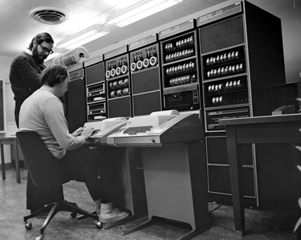 Dennis Ritchie (standing) and Ken Thompson with a PDP-11, circa 1972